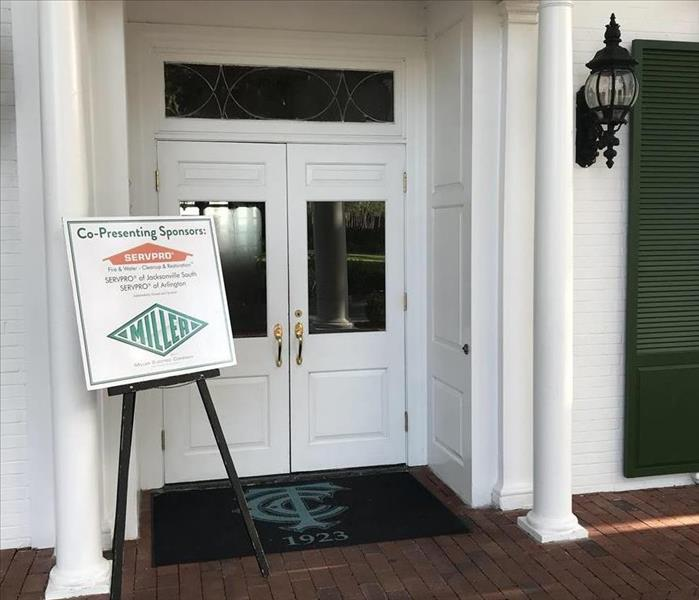 A front door with a sign propped up in front of the door with the words SERVPRO on it.