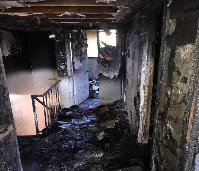 A room in a house covered in soot and smoke damage after a fire